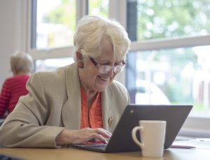 Older lady smiling as she looks at computer tablet